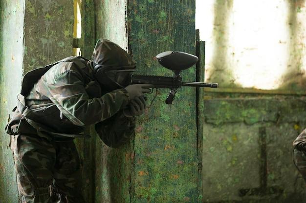 Игрок играет в пейнтбол с ружьем. фото высокого качества