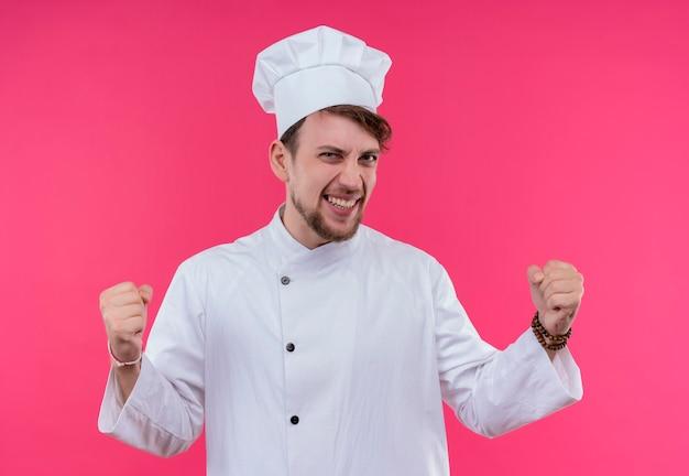 Довольный и счастливый молодой бородатый шеф-повар в белой форме поднимает сжатые кулаки в воздух, глядя на розовую стену