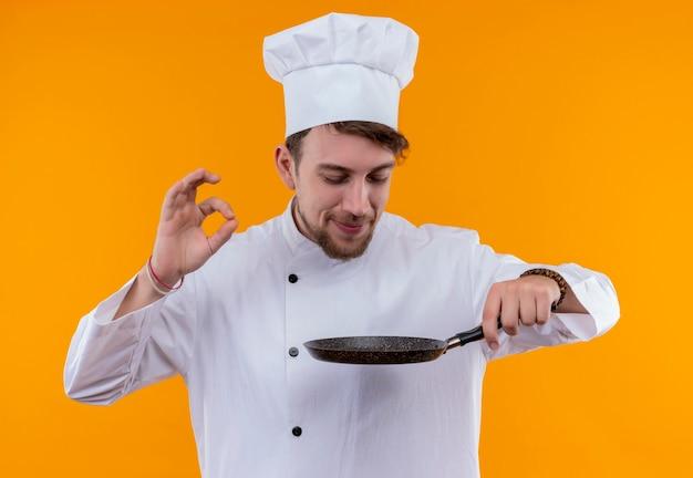 フライパンの匂いを嗅ぎ、オレンジ色の壁においしいokジェスチャーを示す白い制服を着た喜んでいる若いひげを生やしたシェフの男