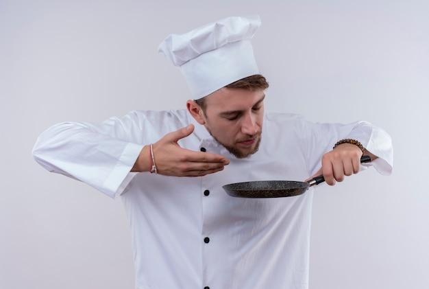 白い壁にフライパンを持って、白い炊飯器の制服と帽子をかぶって料理の匂いを楽しんでいる喜んでいる若いひげを生やしたシェフの男