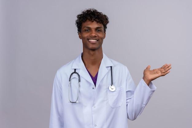 Довольный молодой красивый темнокожий доктор с кудрявыми волосами в белом халате со стетоскопом улыбается и поднимает руку