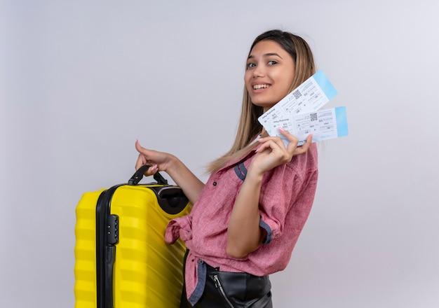Довольная молодая женщина в красной рубашке держит желтый чемодан с билетами на самолет, глядя на белую стену
