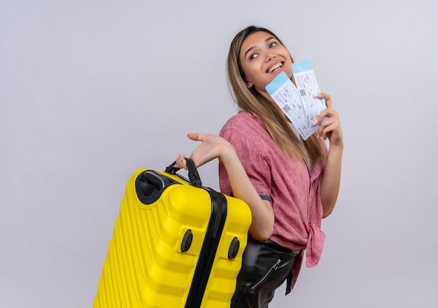 Довольная молодая женщина в красной рубашке держит желтый чемодан с билетами на самолет, глядя в сторону на белой стене