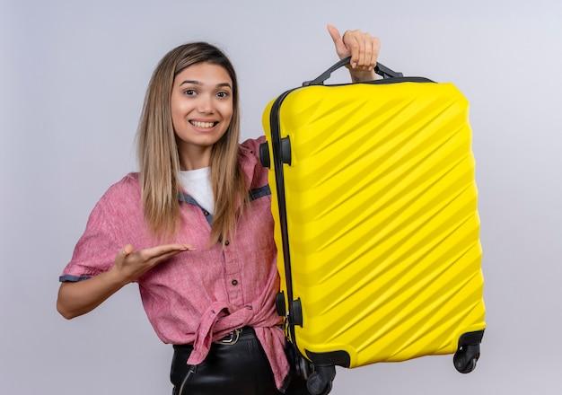 Довольная молодая женщина в красной рубашке показывает свой желтый чемодан, глядя на белую стену
