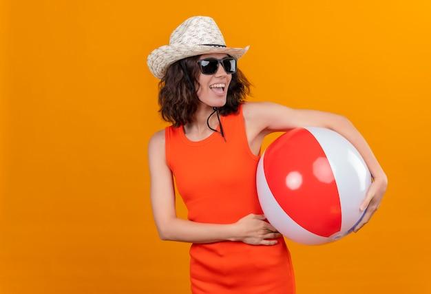 Довольная молодая женщина с короткими волосами в оранжевой рубашке в шляпе от солнца и солнечных очках держит надувной мяч, глядя сбоку