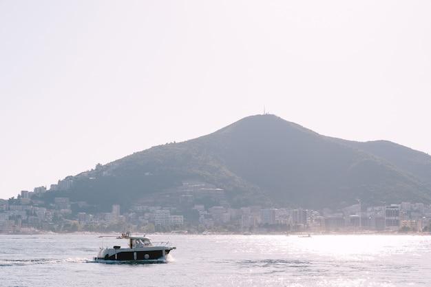 山々に面した海岸線に日よけが付いた遊覧船