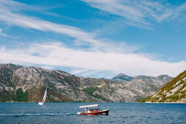 太陽からの日よけが付いた喜びの赤いモーターボートは、街の沖合で人々と一緒に航海します