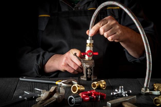 配管工は真ちゅう製の継手を配管ホースに接続します