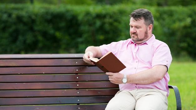 ふっくらとした男がベンチで本を読んでいる