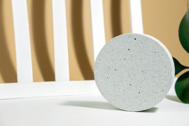 단단한 그림자가 있는 흰색 베이지색 배경에 포장 및 화장품 프레젠테이션을 위해 녹색 잎이 있는 콘크리트로 만든 연단입니다. 흰색 콘크리트 질감, 석재 질감이 있는 제품 디스플레이.