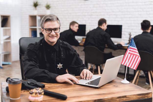 경찰관이 경찰서에서 노트북을 위해 일합니다.