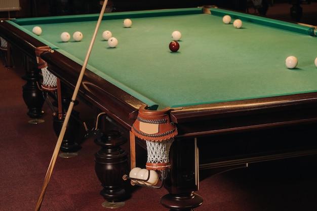 プールクラブですでにプレーされているボールのあるビリヤード台。ビリヤードをプレーする。
