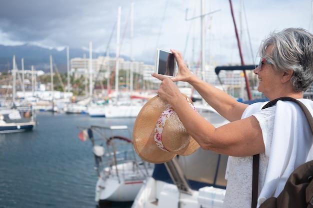ヨットとヨットのある港白髪の年配の女性が風景写真を撮る