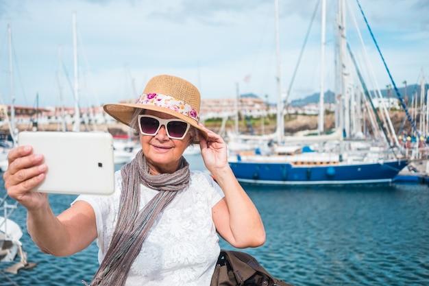 ヨットとヨットのある港。白髪の年配の女性がタブレットで風景を自撮りします。曇りと風の強い日