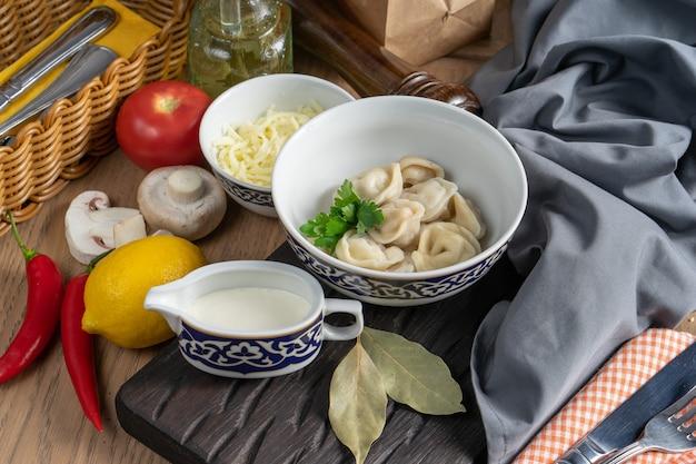 Порция вареных пельменей со сметаной в тарелке с традиционным узбекским