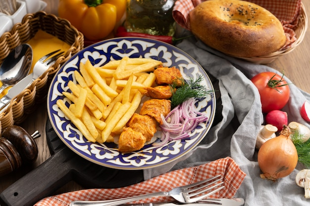 伝統的なウズベキスタンのプレートにフライドポテト、玉ねぎ、ディルを添えたチキンシシカバブの一部