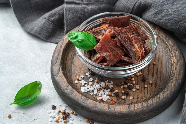 Порция сушеного мяса с перцем, солью и свежим базиликом на серой стене. вид сбоку, крупный план.