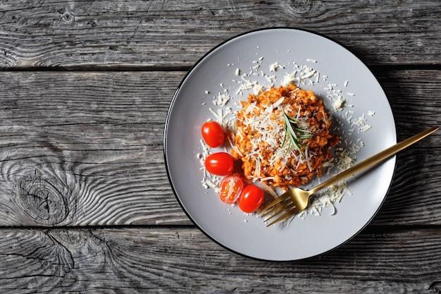 Порция ризотто из говяжьего фарша, посыпанная тертым пармезаном, на тарелке, итальянская кухня, плоская планировка, свободное место