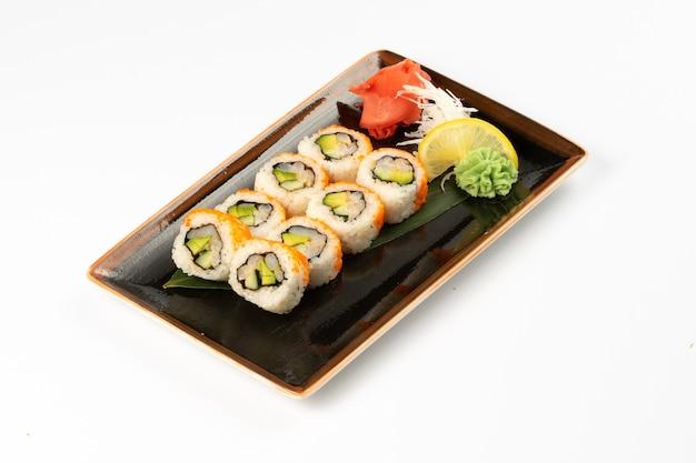 白い背景の長方形のセラミックプレートに日本のおかずの品揃えと巻き寿司の一部