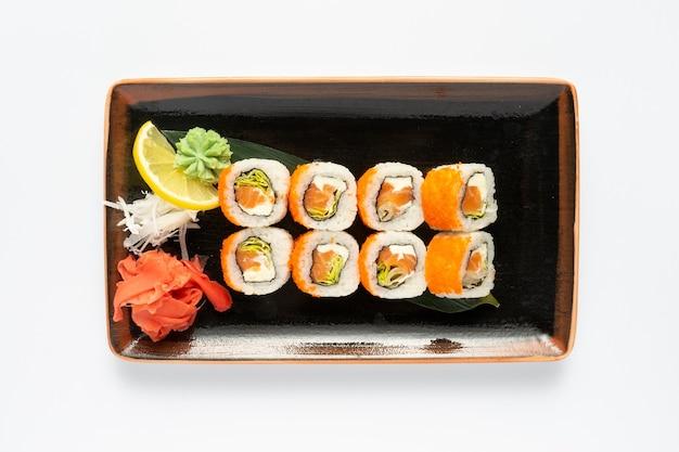 흰색 배경에 직사각형 세라믹 접시에 일본식 반찬의 구색과 함께 마키 스시의 일부
