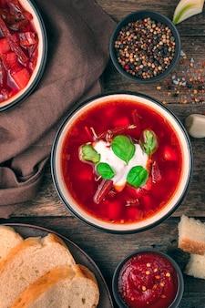 토마토와 비트 뿌리, 사워 크림과 바질이 들어간 야채 수프의 일부. 신선하고 맛있는 보르시. 수직 평면도.