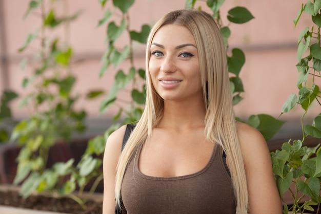 屋外の美しい金髪の若い白人女性の肖像画。若い笑顔の女性屋外ポートレート