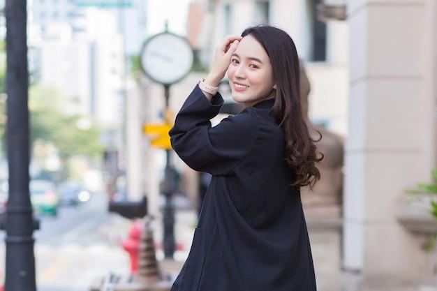 Портрет красивой длинноволосой азиатской женщины в черном пальто, идущей и счастливой