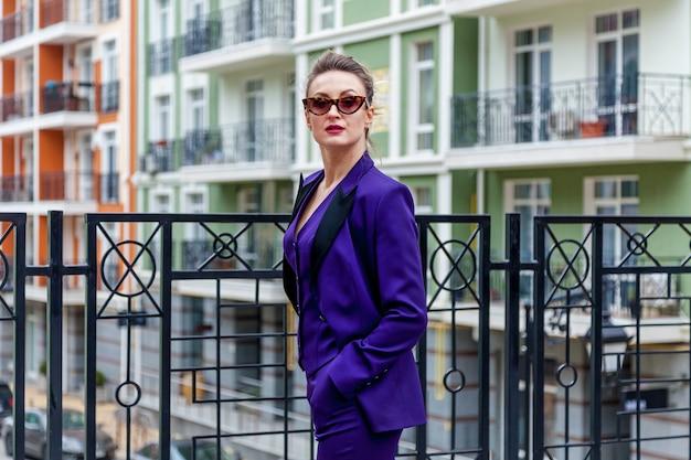 보라색 양복과 안경을 쓴 금발 여성의 초상화는 장식 요소가 있는 건물 발코니에서 사진 작가를 위해 포즈를 취합니다....