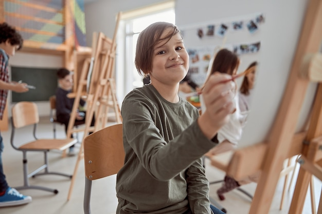 Портрет мальчика на групповом уроке рисования в светлом современном классе