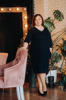 У кресла в интерьере стоит портрет бизнесвумен в черном платье с бусами на шее.