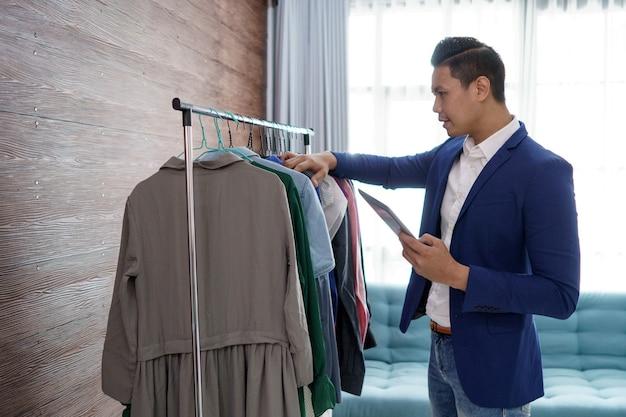 쾌활한 옷 가게 주인의 초상화. 상점의 재고를 확인하는 사람