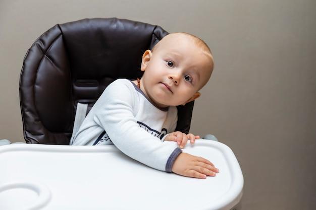 유아용 의자에 앉아 귀여운 호기심 사랑스러운 아기의 초상화