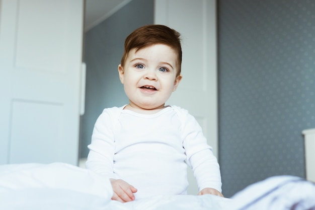 침대에 흰색 바디 슈트 좌석에 귀여운 유아 아기 소년의 초상화와 집에서 침실에서 행복한 아기 얼굴을 웃고