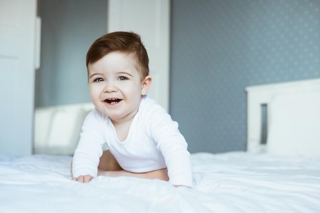 침대에 흰색 bodyuit 좌석과 웃음에 귀여운 유아 아기 소년의 초상화. 행복한 아기 얼굴은 집 측면보기에서 침실에서 카메라를 봐