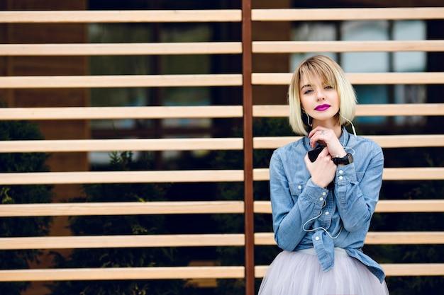 Портрет мечтательной блондинки с ярко-розовыми губами и обнаженным макияжем, слушающей музыку на смартфоне с полосатыми деревянными балками сзади