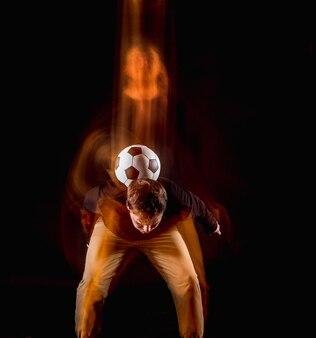 Портрет вентилятора с мячом на сером студийном фоне. концепция фристайл. техника стрельбы стробоскопом