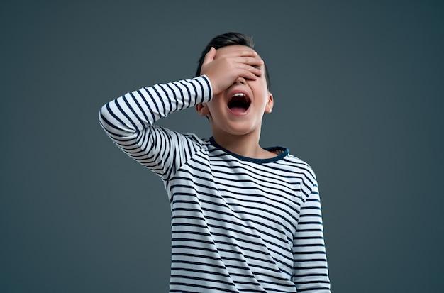 그의 손으로 눈을 감고 회색에 비명을 지르는 줄무늬 스웨터를 입은 세련된 소년의 초상화.