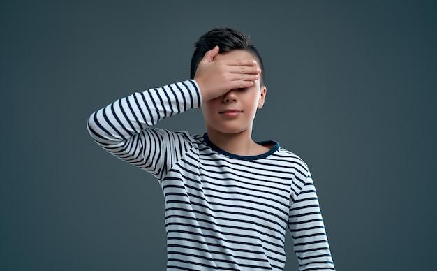 회색에 손으로 눈을 감은 줄무늬 스웨터를 입은 유행 소년의 초상화.