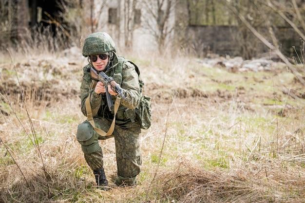 乾いた草の真っ只中にある戦場でライフルを狙う装備の整った兵士の肖像画。