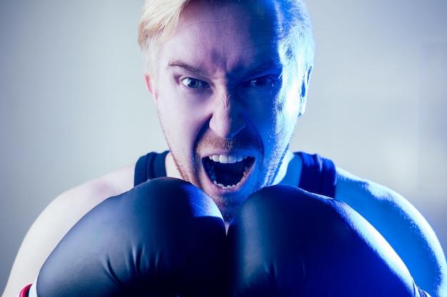 체육관에서 스포츠를 하는 격렬하고 사악한 남자 권투 선수의 초상화. 어두운 배경에 권투 선수와 권투 장갑입니다. 남자가 친다. 손에 붕대.