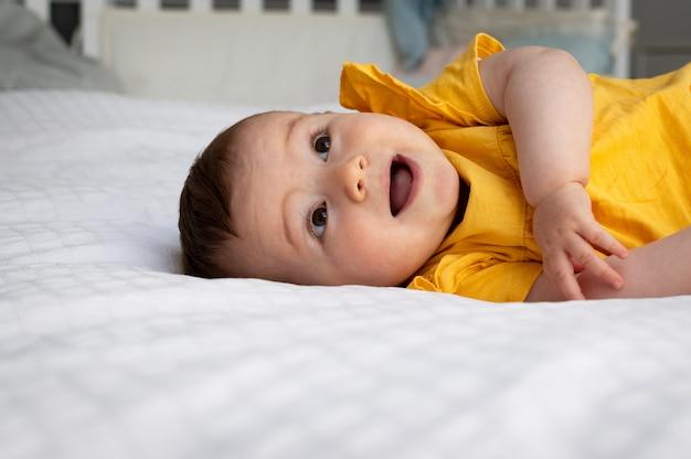Портрет лица счастливого ребенка, лежа на кровати, детство и люди концепции