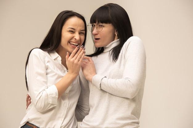 Портрет счастливой матери и дочери в студии на сером фоне. концепция человеческих положительных эмоций и мимики