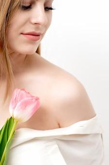 닫힌 된 눈을 가진 행복 한 젊은 백인 여자와 복사 공간 흰색 배경에 대해 한 핑크 튤립의 초상화