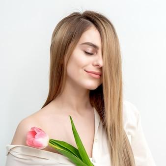 Портрет счастливой молодой кавказской женщины с закрытыми глазами и одним розовым тюльпаном на белом фоне с копией пространства
