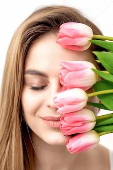 Портрет счастливой молодой кавказской женщины с закрытыми глазами и розовыми тюльпанами закрывает лицо на белом фоне