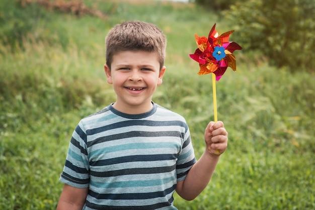 Портрет счастливого сладкого мальчика, держащего маховик в парке. ребенок играет с мельницей