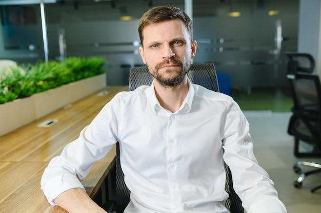 Портрет мужчины в офисе, разговаривающего по видеосвязи онлайн-конференции фото высокого качества