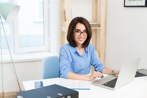 オフィスのテーブルに座っているかわいい女の子の肖像画。彼女はラップトップで作業していて、カメラに微笑んでいます。