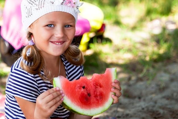 Портрет маленькой симпатичной маленькой девочки, которая ест большой кусок арбуза на пикнике в летний теплый день, на заднем плане пляж и зеленая трава