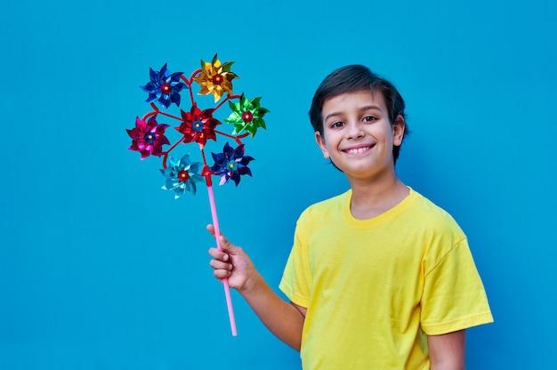 그의 손에 멀티 바람개비를 들고 노란색 셔츠에 웃는 소년의 초상화. 파란색 벽에. 공간 복사